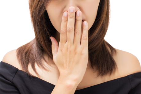 woman with hand covering mouth